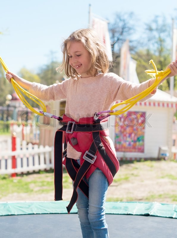 Stock image of 'Little girl on bungee trampoline with cords. '
