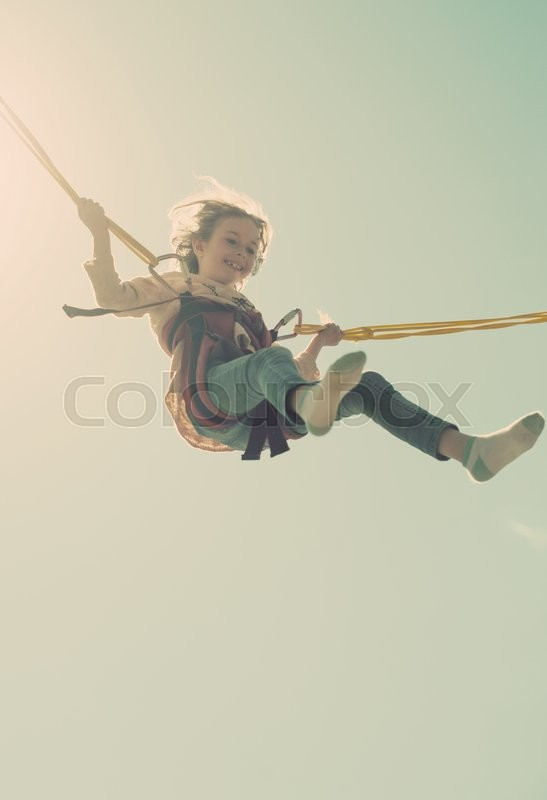 Stock image of 'Little girl on bungee trampoline with cords. Place for text.'
