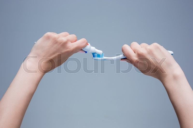 Stock image of 'Toothbrush in woman's hands on gray background'