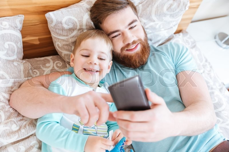 Stock image of 'Top view of cheerful bearded father using smartphone and lying on bed with little son '