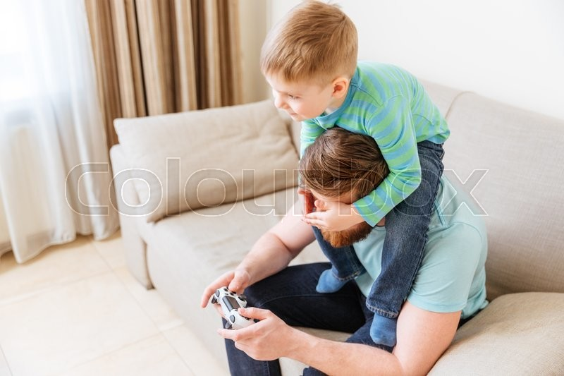 Stock image of 'Handsome young man sitting on sofa and playing computer games while his little son covering his eyes'