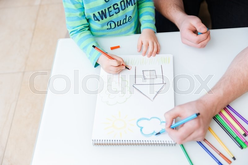 Stock image of 'Top view of hands of little son and his father drawing with colorful markers on the table'