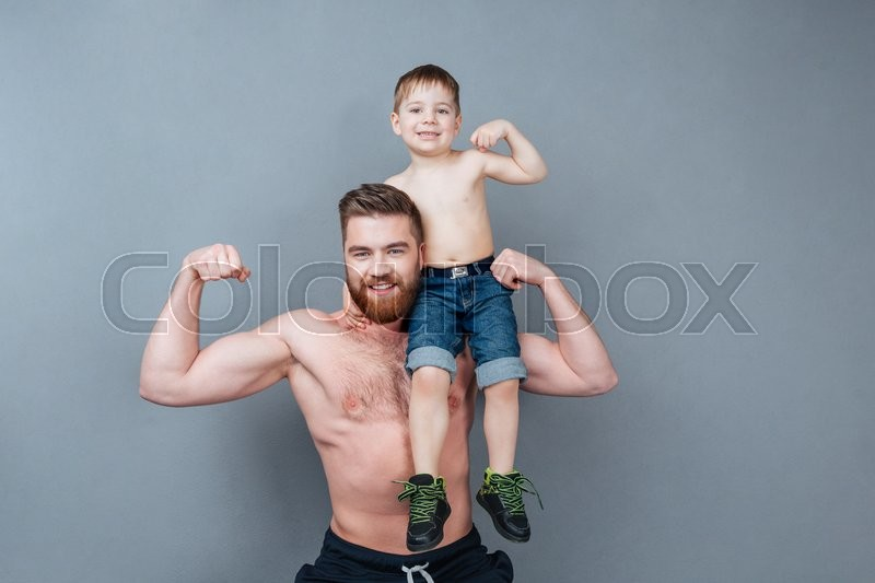 Handsome cheerful strong man holding his little son on his shoulder and showing biceps, stock photo