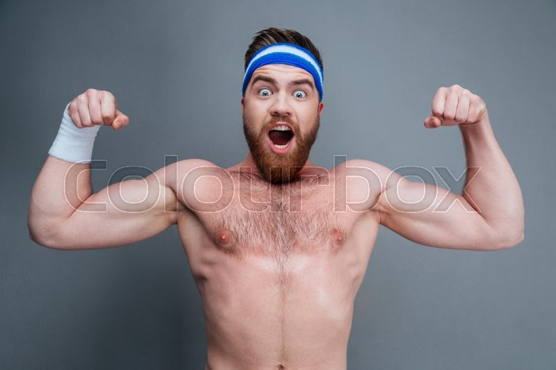 Stock image of 'Happy amazed young sportsman standing and showing biceps over grey background'