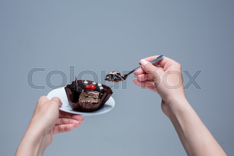 Stock image of 'Female hands keeping cake with spoon on gray background'