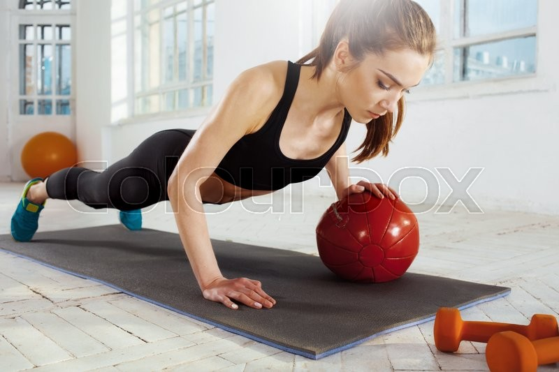 Stock image of 'Beautiful young slim woman doing some gymnastics at the gym with medball'