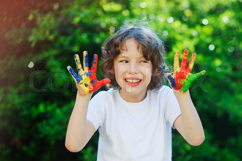 Stock image of 'The boy's hand in the paint. He likes it. Child makes faces with pleasure.'