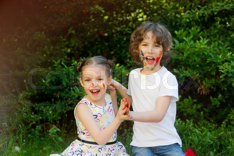 Stock image of 'Children soiled with paint, having fun and look into the camera. Kids has fun with a painting outdoor. Children's creativity. Art for baby. Emotions. Children playing. Delight.'