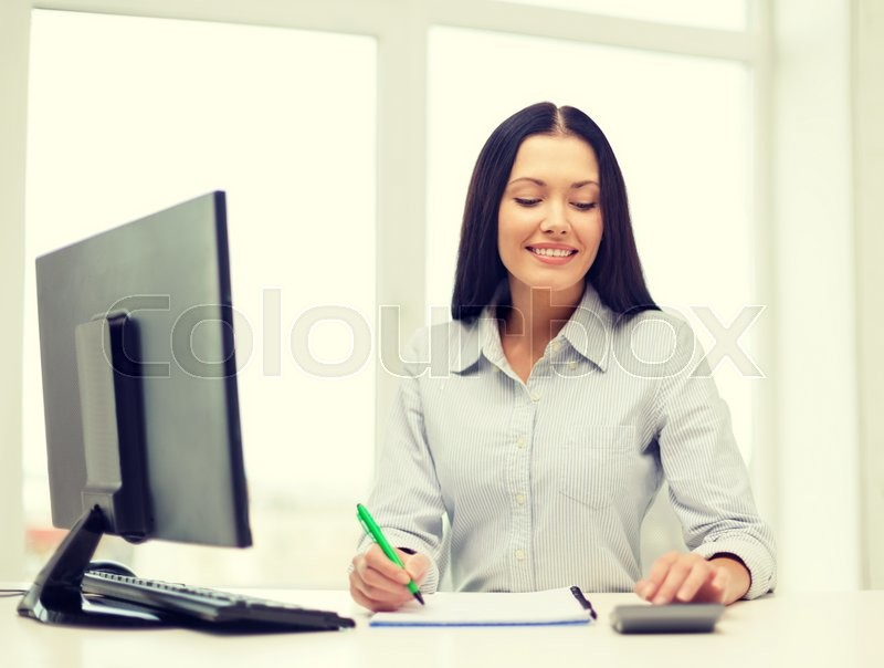 Stock image of 'business, education and technology concept - happy businesswoman with computer, notebook and calculator in office'