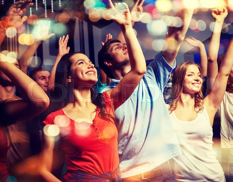Stock image of 'party, holidays, celebration, nightlife and people concept - smiling friends waving hands at concert in club'