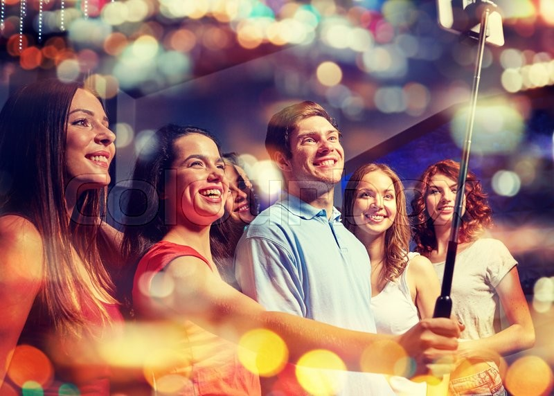 Party, technology, nightlife and people concept - smiling friends with smartphone and monopod taking selfie in night club with holidays lights, stock photo
