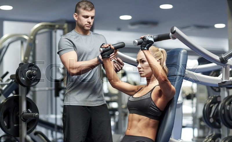 Stock image of 'sport, fitness, bodybuilding, teamwork and people concept - young woman and personal trainer flexing muscles on gym machine'