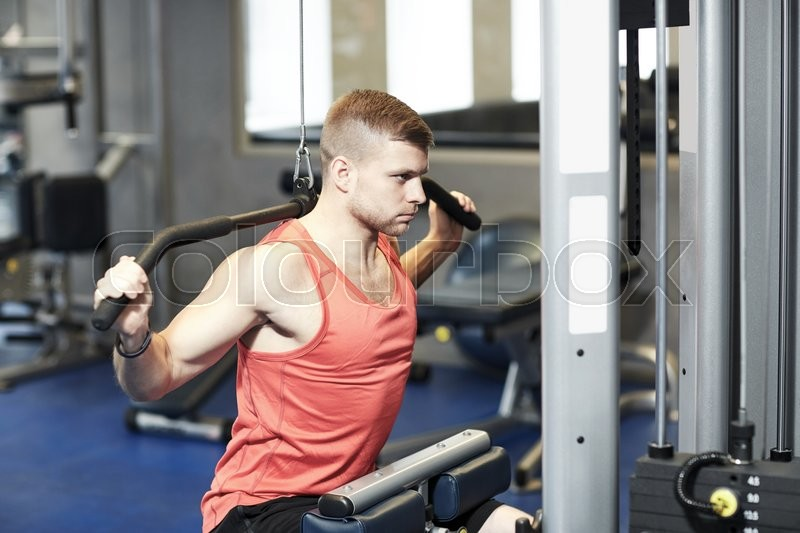Stock image of 'sport, fitness, bodybuilding, lifestyle and people concept - man exercising and flexing muscles on cable machine in gym'
