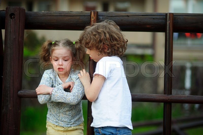 Stock image of 'Children play on the playground. On the girl's face with tears. Boy it comforting'
