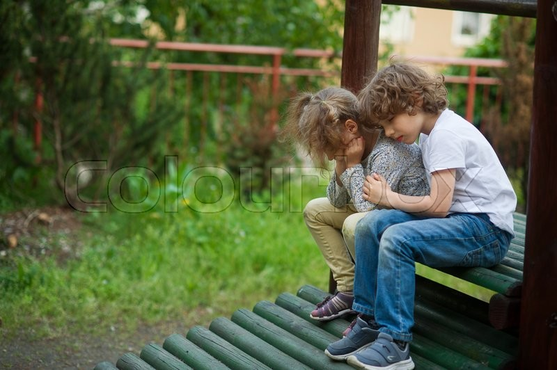 Stock image of 'Kids sad sitting together on the bench. The boy hugs a girl. They bowed their heads'