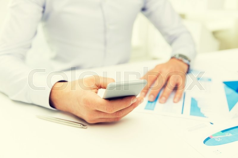 Stock image of 'business, deadline, people and technology concept - close up of businessman with smartphone'