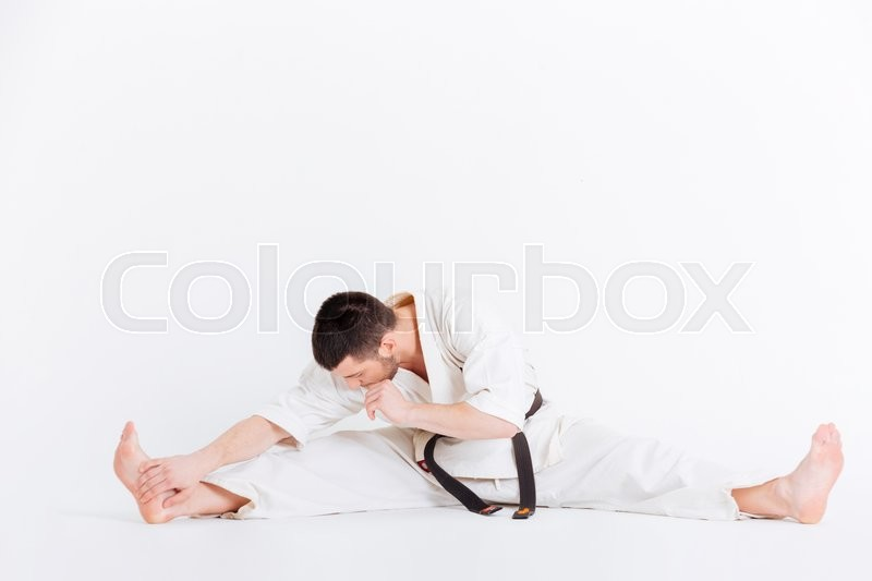 Stock image of 'Man in kimono limbering up isolated on a white background'