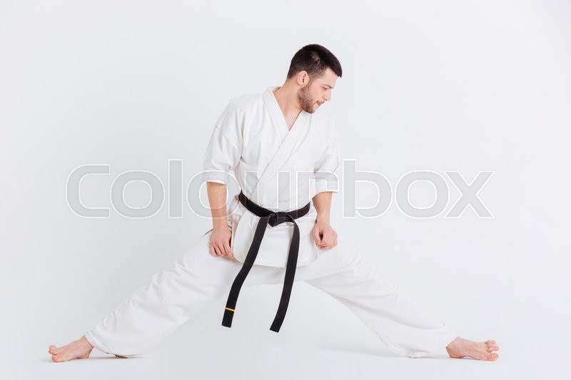 Stock image of 'Full length portrait of a man in kimono doing stretching exercises isolated on a white background'