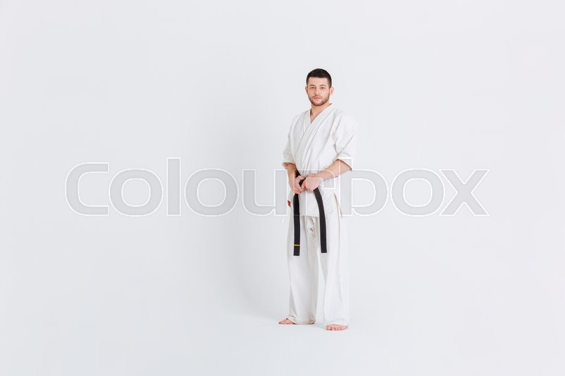 Stock image of 'Full length portrait of a man in kimono standing isolated on a white background'