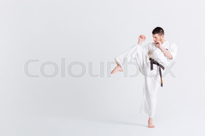 Stock image of 'Male fighter in kimono posnig isolated on a white background'