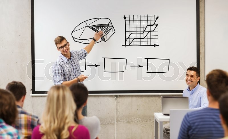 Stock image of 'education, high school, economics and people concept - student standing with remote control in front of teacher and classmates and showing scheme on white board in classroom'