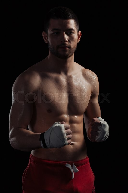 Stock image of 'Handsome male boxer standing over black background'