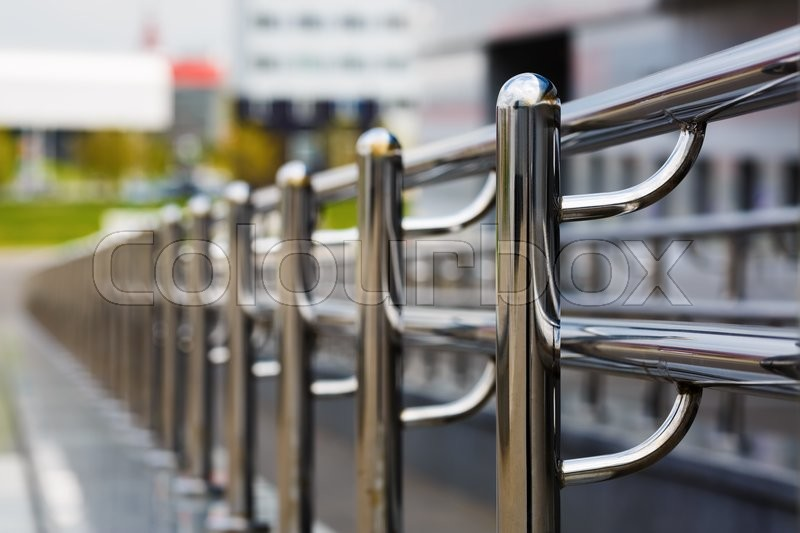 Stock image of 'Chromium metal fence with handrail. Chrome-plated metal railings. Shallow depth of field. Selective focus.'