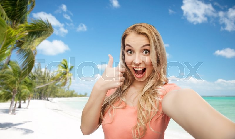 Stock image of 'travel, tourism, emotions, expressions and people concept - happy smiling young woman taking selfie and showing thumbs up over exotic tropical beach with palm trees background'