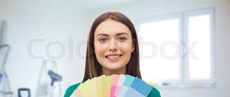 Stock image of 'repair, renovation, decoration, design and people concept - smiling young woman with color swatches or samples over home background'