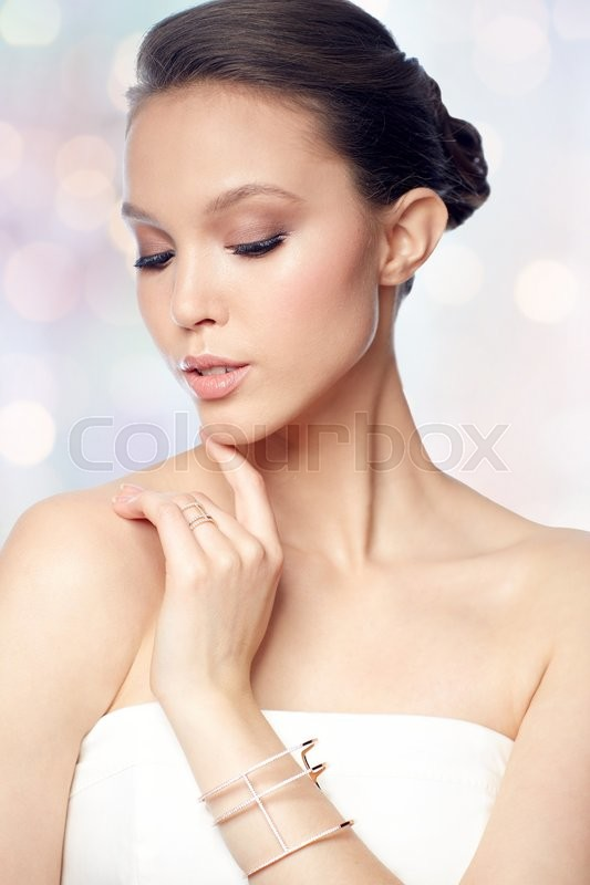 Stock image of 'beauty, jewelry, wedding accessories, people and luxury concept - beautiful asian woman or bride with golden ring and bracelet over holidays lights background'