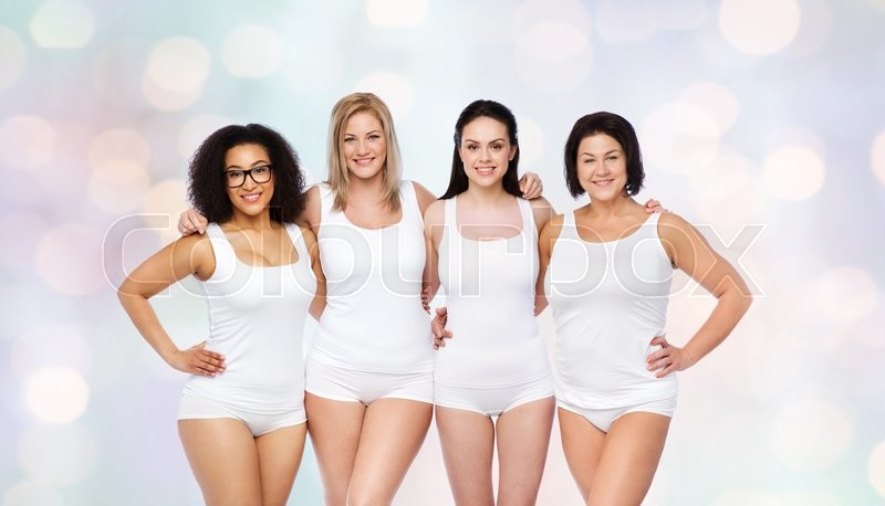 Stock image of 'friendship, beauty, body positive and people concept - group of happy women different in white underwear over holidays lights background'