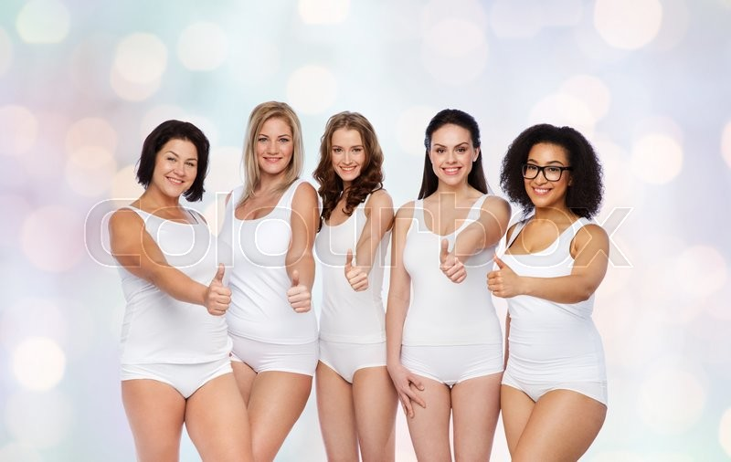Stock image of 'gesture, friendship, beauty, body positive and people concept - group of happy different women in white underwear showing thumbs up over holidays lights background'
