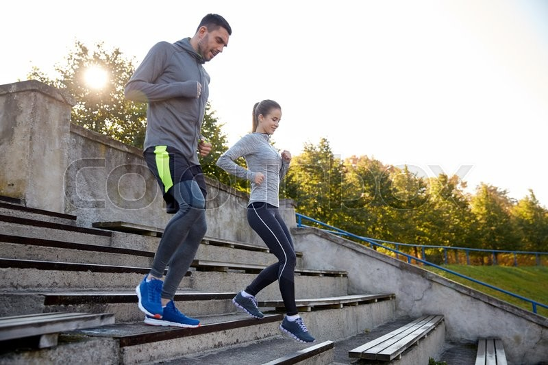 Stock image of 'fitness, sport, people and lifestyle concept - couple running downstairs on stadium'