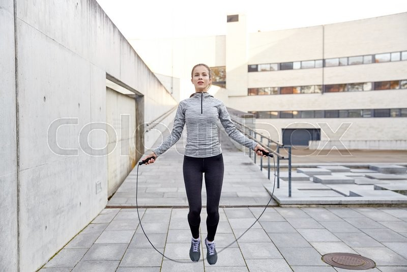 Stock image of 'fitness, sport, people, exercising and lifestyle concept - woman skipping with jump rope outdoors'
