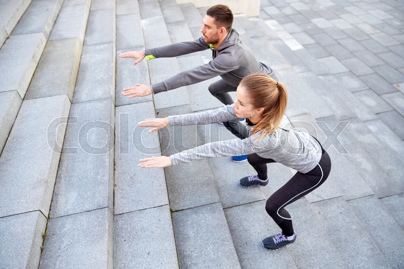 Stock image of 'fitness, sport, people, exercising and lifestyle concept - couple doing squats on city street stairs'