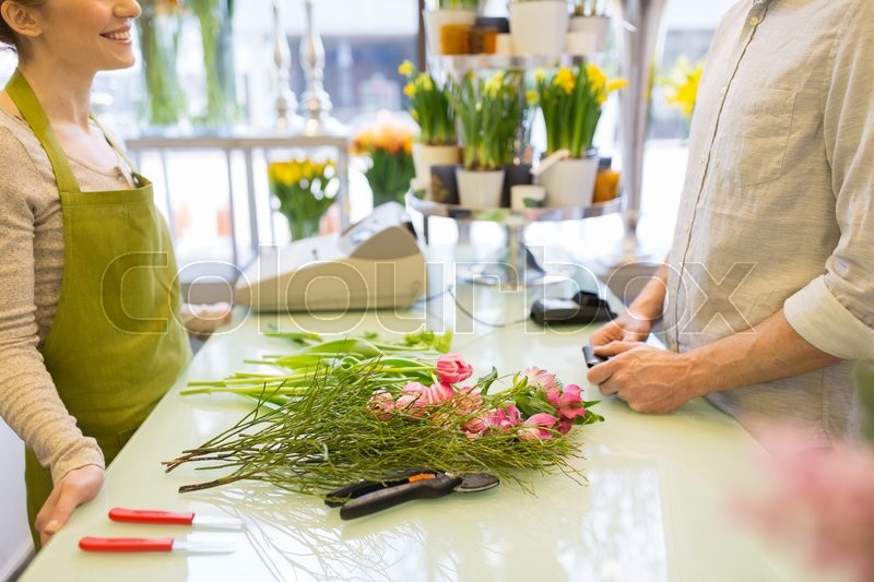 Stock image of 'people, shopping, sale, floristry and consumerism concept - close up of happy florist woman making bouquet for and man or customer at flower shop'