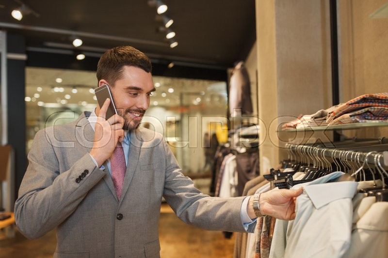 Stock image of 'sale, shopping, fashion, communication and people concept - happy young man or businessman calling on smartphone and choosing clothes at clothing store'