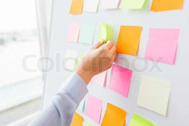 Stock image of 'office, business, people and education concept - close up of hand with pen pointing to blank sticker on white board'