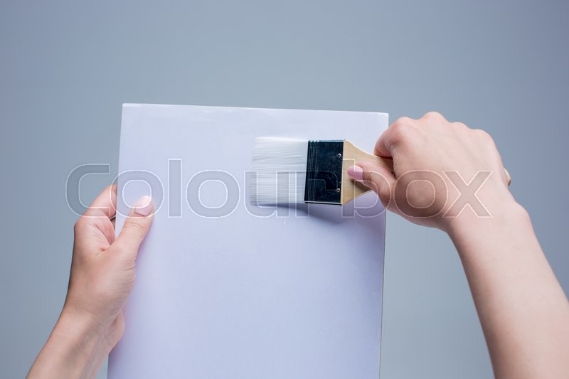 Stock image of 'The female hands holding painting brush on white canvas'