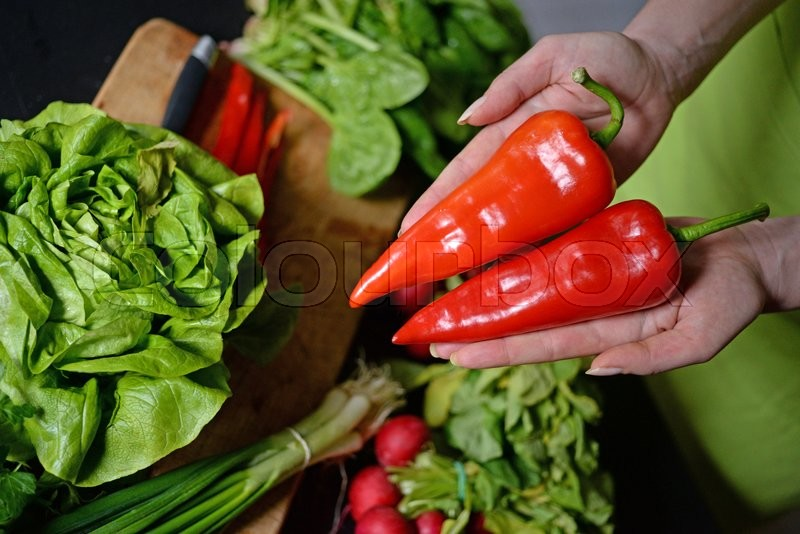 Stock image of 'Fresh red pepper radish in woman's hand'