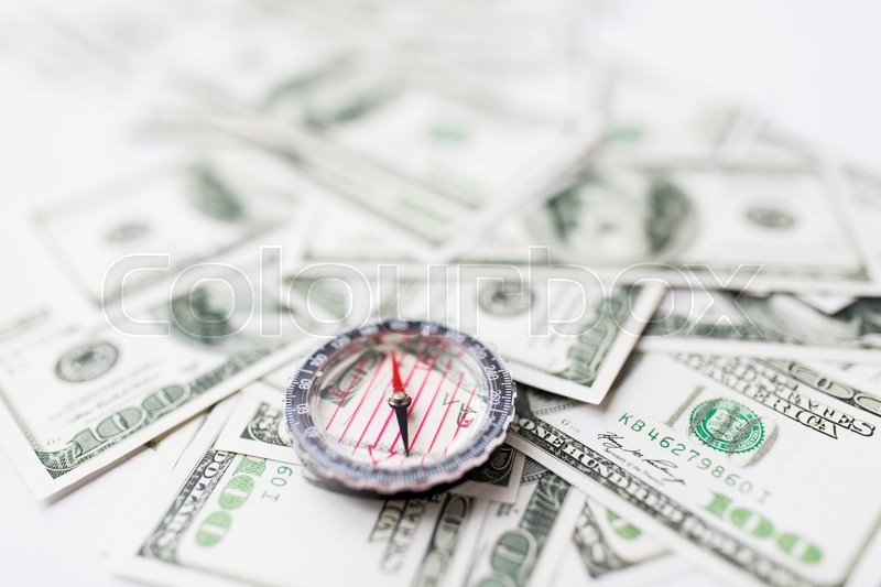 Stock image of 'business, economy, finance and investment concept - close up of compass and dollar money'