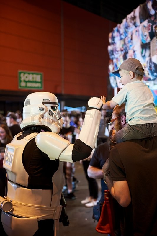 Editorial image of 'STRASBOURG, FRANCE - MAY 8, 2016: Darth Vader shaking hand with little fan boy at the open market Digital Game Manga Show'