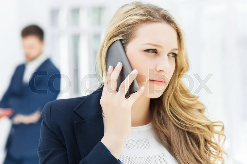 Stock image of 'Portrait of businesswoman talking on mobile phone in office'