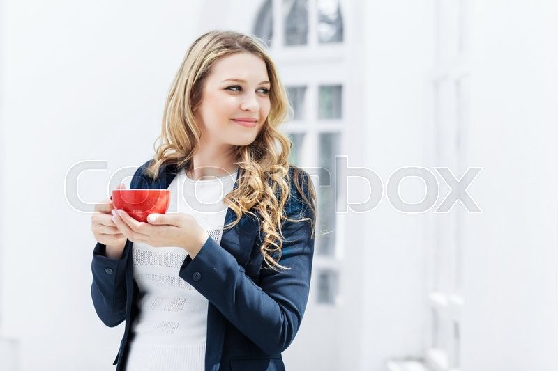 Stock image of 'The smiling female office worker having coffee break in office'