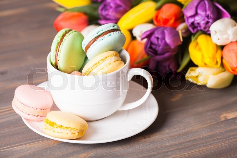 Stock image of 'Color macaroons in a cup and flowers on the background'
