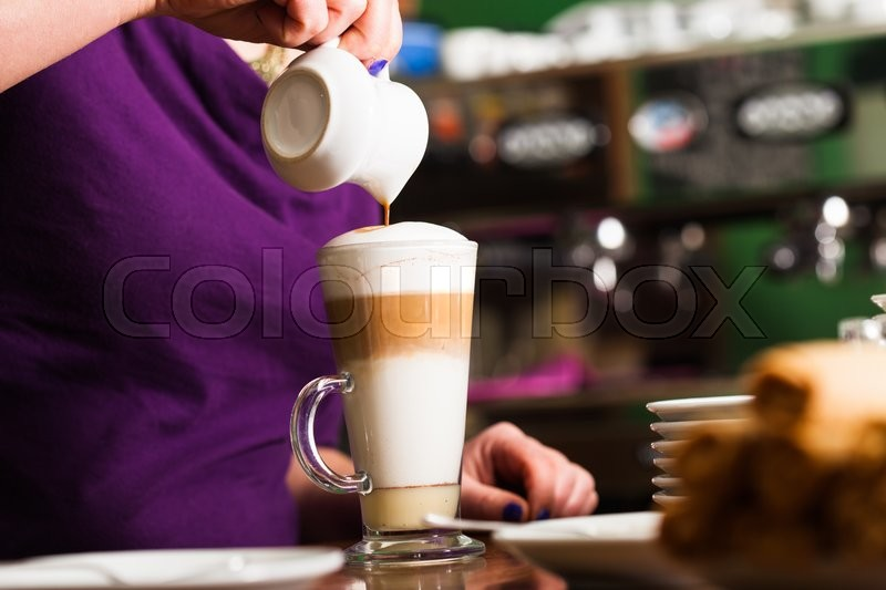 Stock image of 'Barista is pouring coffee in milk - preparing coffe latte'