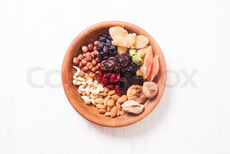 Stock image of 'Dry fruits and nuts in bowl on wooden table. Copy space background - close up healthy sweets'