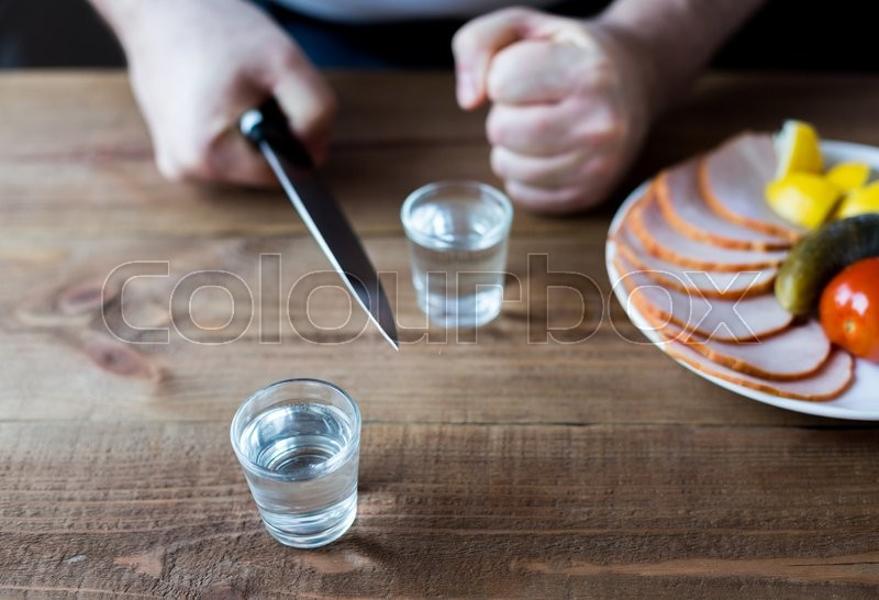 Stock image of 'Shot glasses of vodka on a wooden table, bottle and a plate of ham. A knife in the hand.'