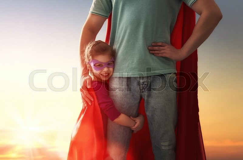 Stock image of 'Happy loving family. Father and his daughter child girl playing outdoors. Daddy and his child girl in an Superhero's costumes. Concept of Father's day.'