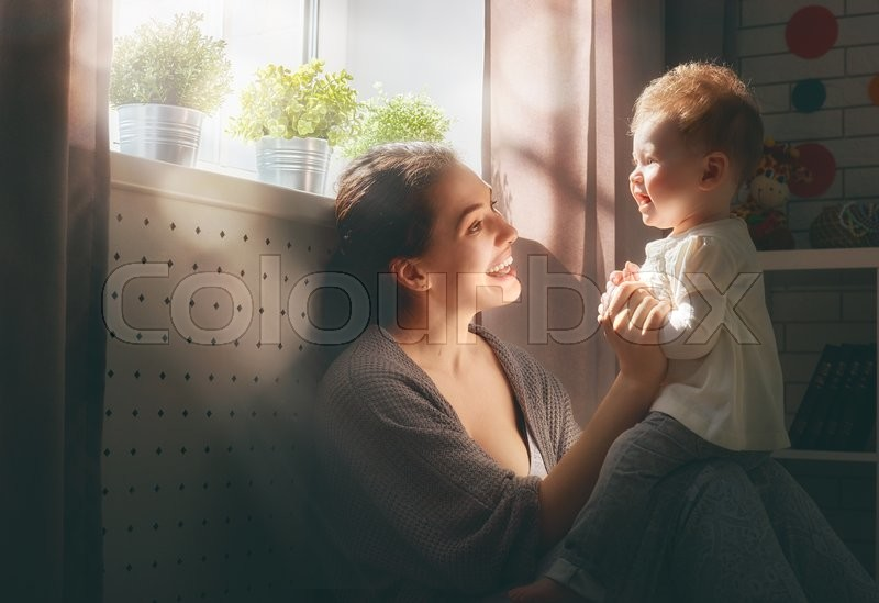 Stock image of 'happy loving family. mother playing with her baby in the bedroom.'